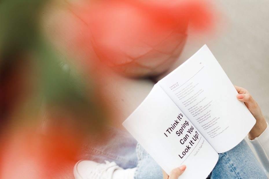 """Girl sitting underneath flowers with Capsule Stories Spring 2021 Edition open to the poem """"I Think It's Spring, Can You Look It Up?"""" by Natalia A. Pagán Serrano"""