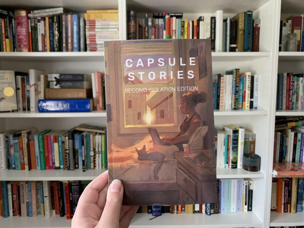capsule stories second isolation edition held by hand in front of bookshelf