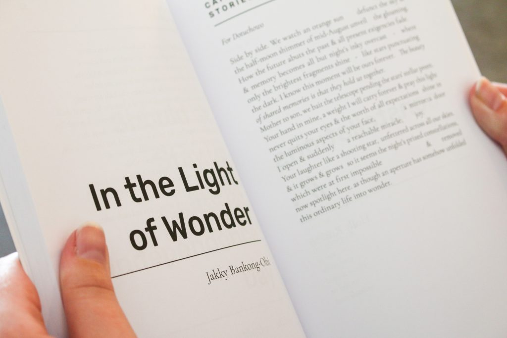 """Hands holding open Capsule Stories Summer 2021 Edition to the poem """"In the Light of Wonder"""" by Jakky Bankong-Obi."""