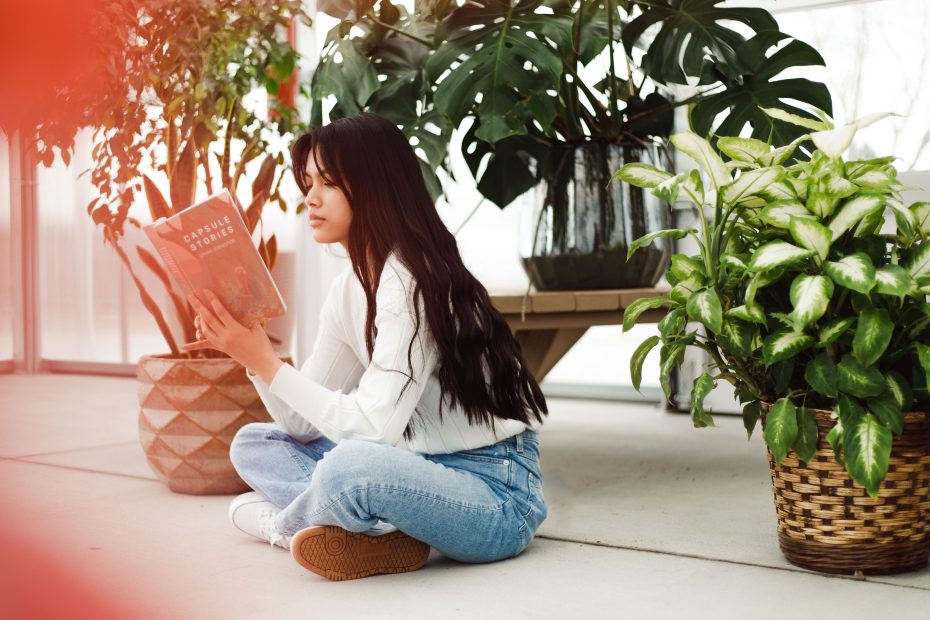 girl in jeans and a white shirt sitting on the ground reading a book, surrounded by plants