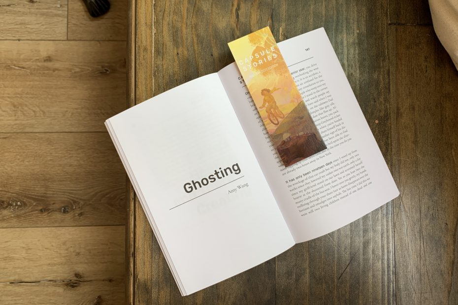 """Capsule Stories Autumn 2021 Edition open on a wood bench to Amy Wang's story """"Ghosting,"""" with a Capsule Stories bookmark sitting on the page."""